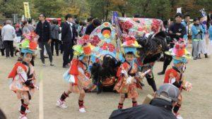 獅子の前で踊る華やかな子どもがキョウクチ